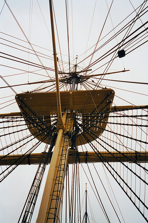 Mast of a sailing ship with the look-out and many thick and thin ropes which are tightend up in different directions.