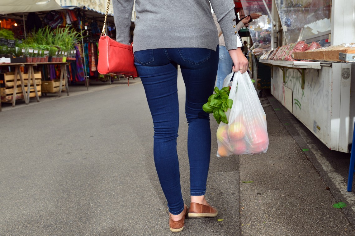 At the market, a woman carries a plastic bag of groceries.